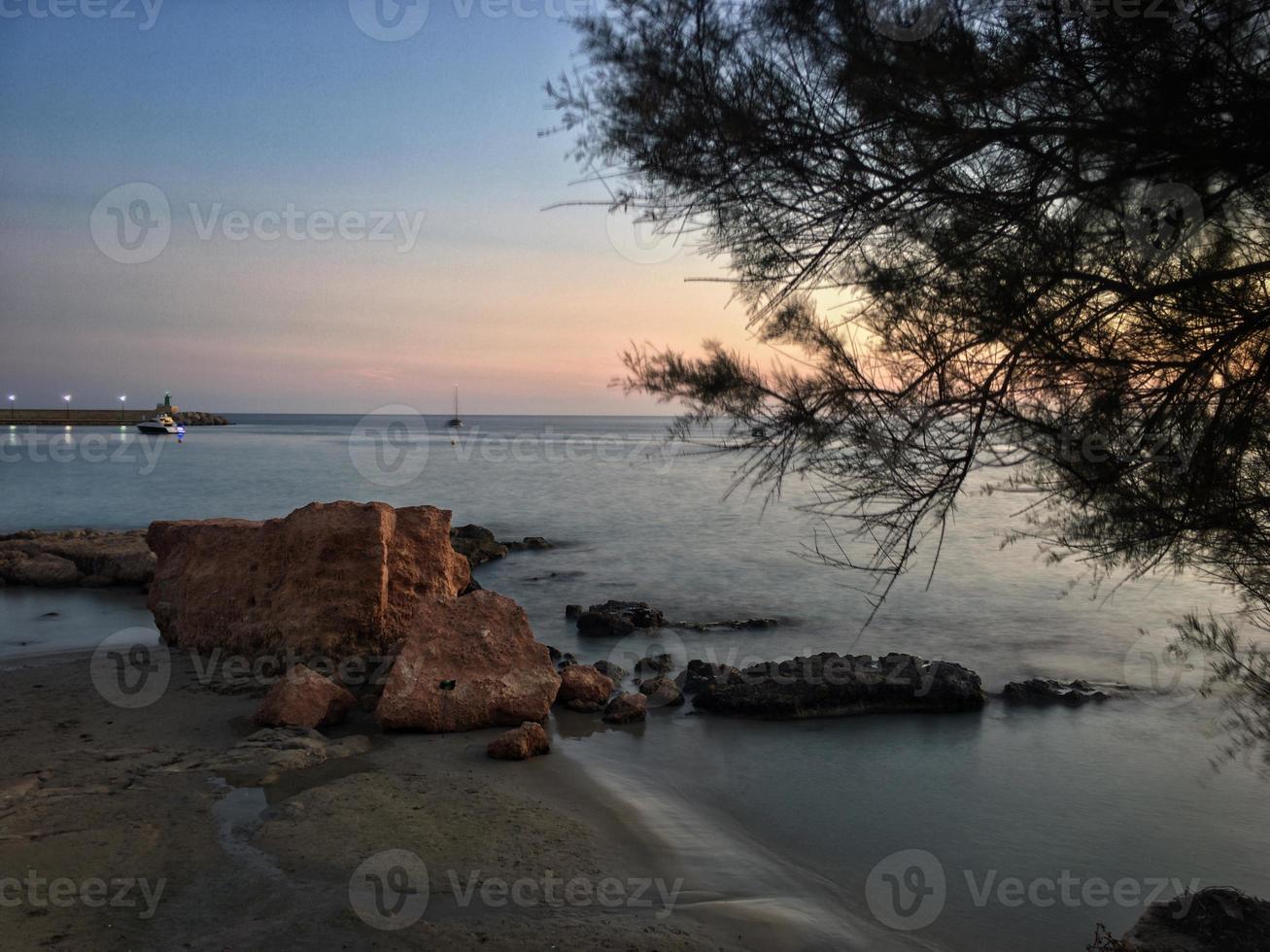 Mittelmeerstrand ohne Menschen bei Sonnenuntergang in Calpe, Alicante foto