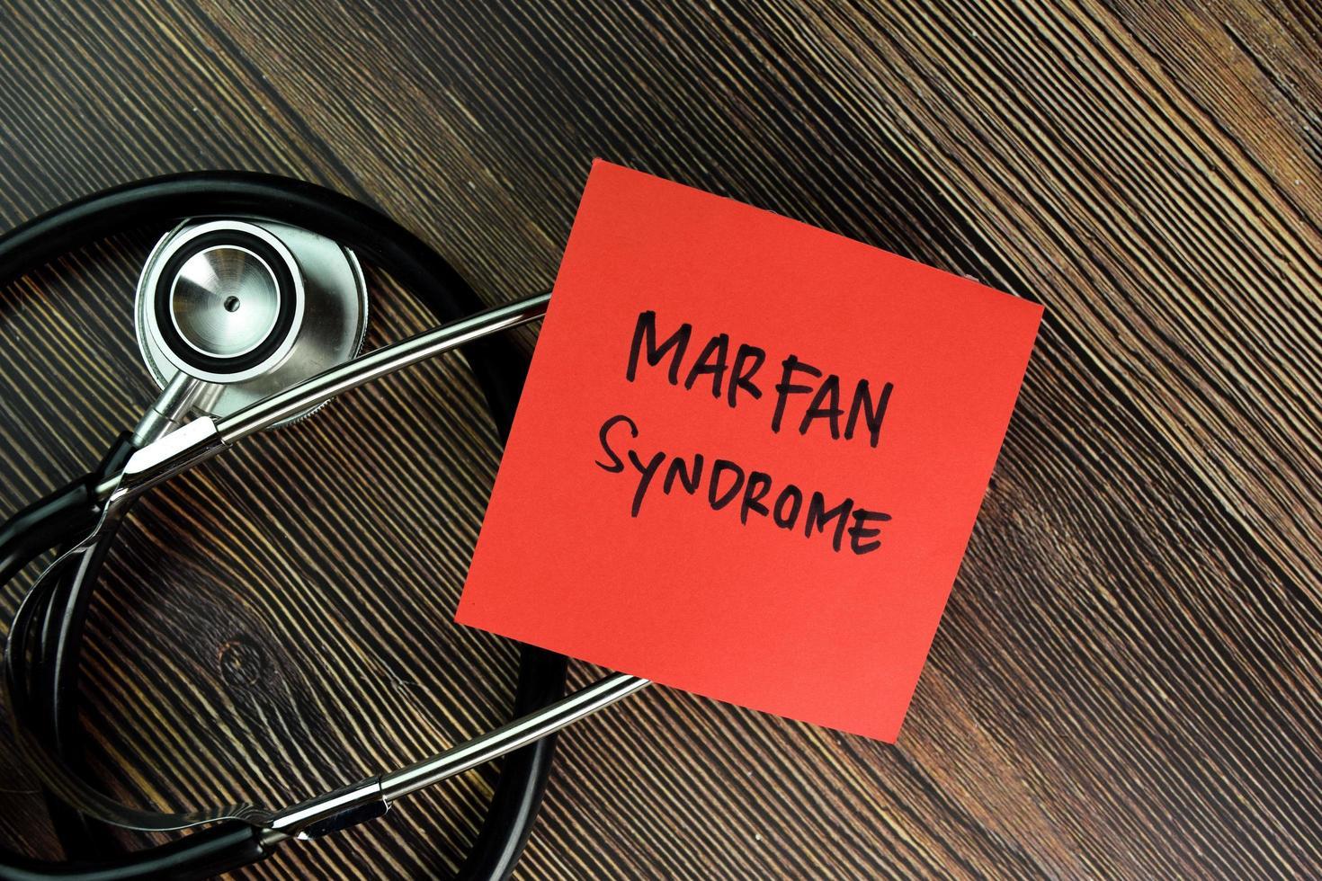 Marfan-Syndrom geschrieben auf Haftnotiz isoliert auf Holztisch foto
