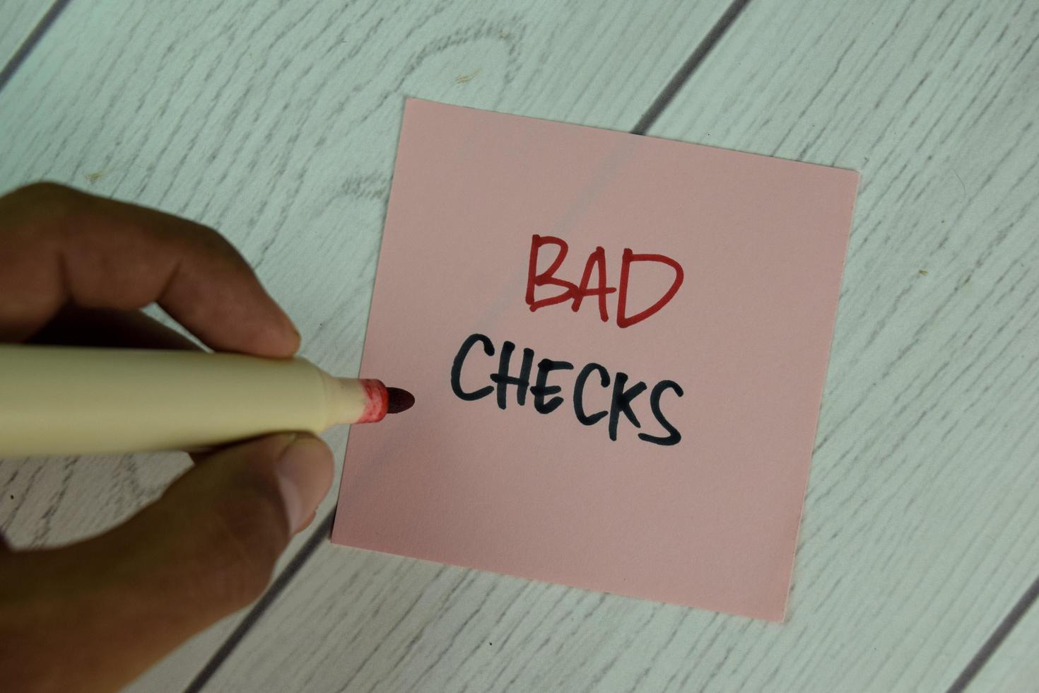 schlechte Schecks geschrieben auf Haftnotiz isoliert auf Holztisch foto