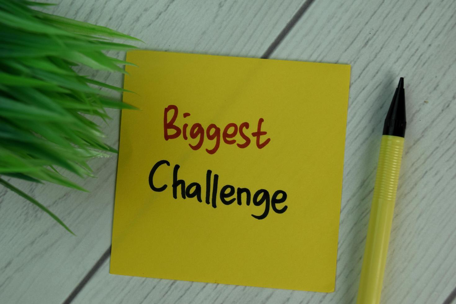 größte Herausforderung geschrieben auf Haftnotiz isoliert auf Holztisch foto