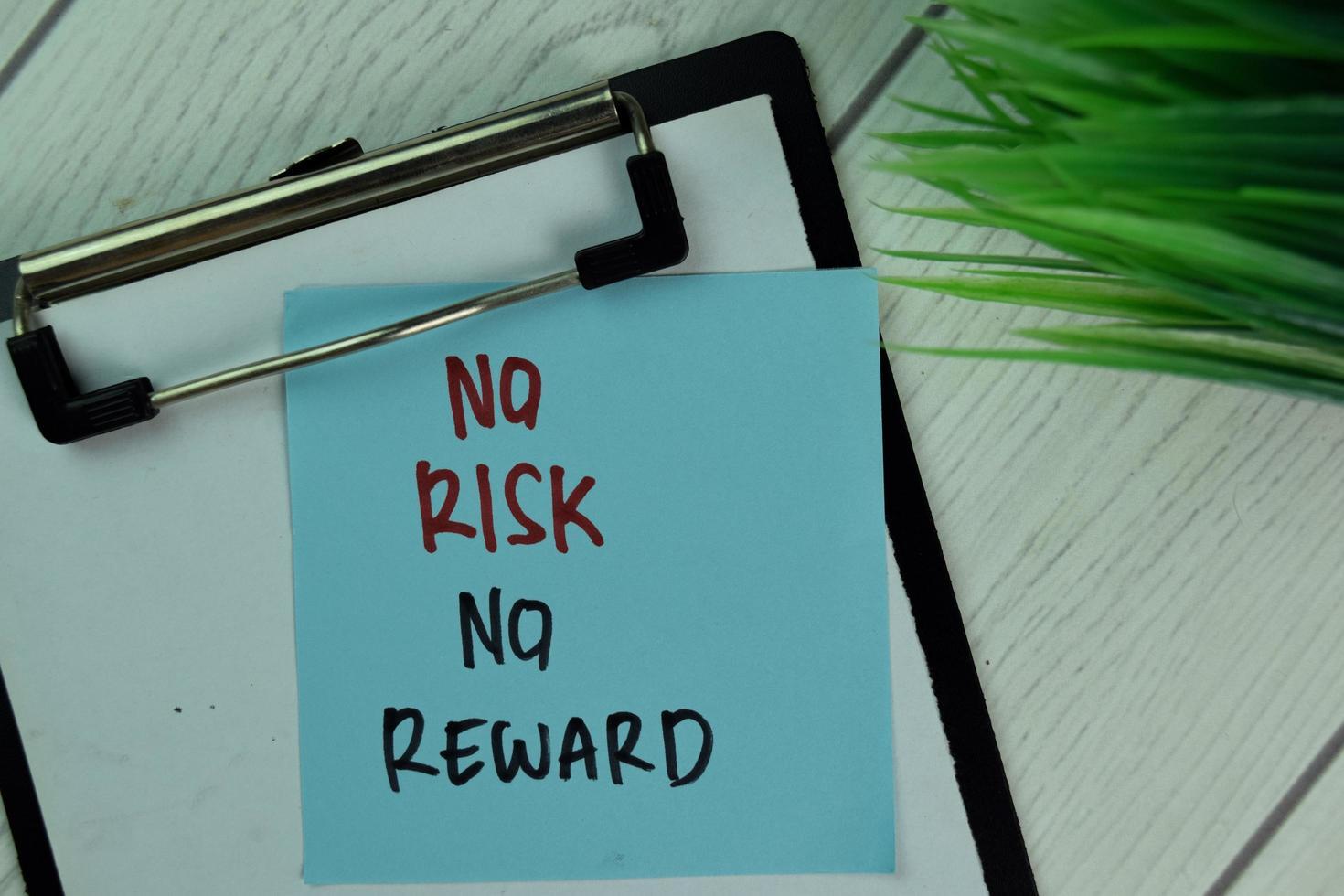 Kein Risiko, keine Belohnung auf Haftnotiz, isoliert auf Holztisch foto