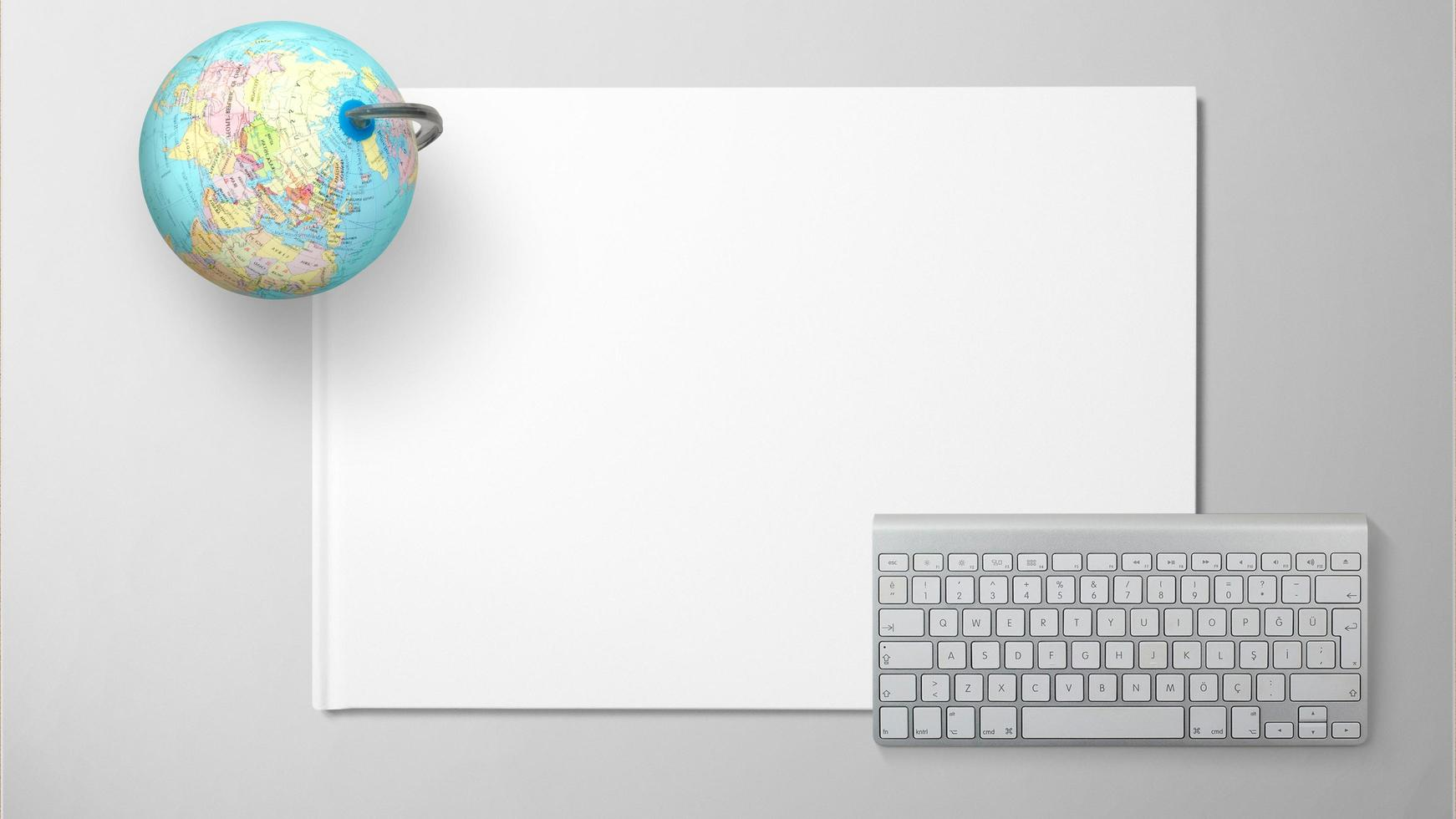 Globus mit Computertastatur auf weißem Papier auf lokalisiertem Hintergrund foto