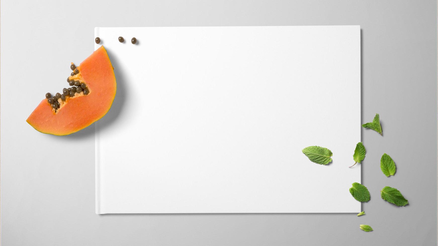 Papaya und Minze auf weißem Papier auf lokalisiertem Hintergrund foto