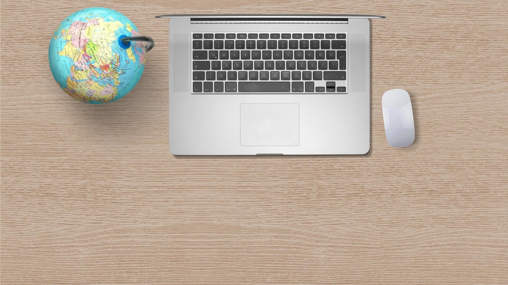 Globus mit Computer-Laptop auf weißem Papier auf hölzernem Hintergrund foto