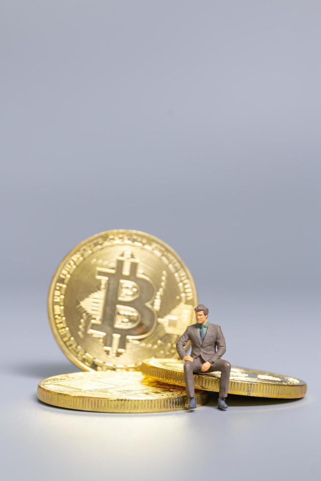 Miniaturgeschäftsmann, der auf Bitcoin-Münzen sitzt, zukünftiges Investitionskonzept foto