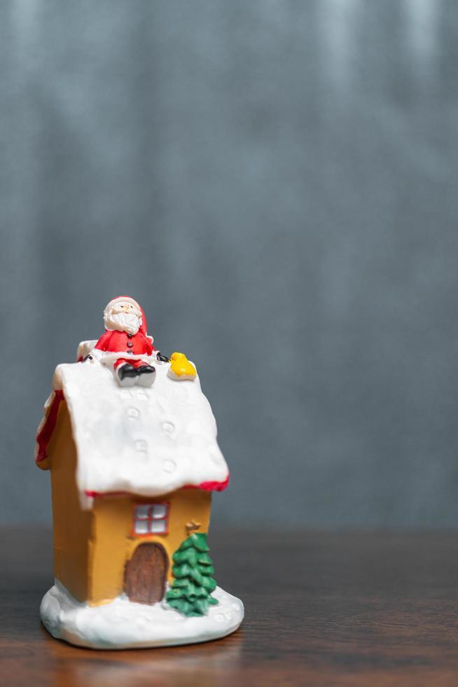 Miniatur-Weihnachtsmann, der auf einem Dach sitzt, Weihnachtslegende und frohe Feiertagskonzept foto