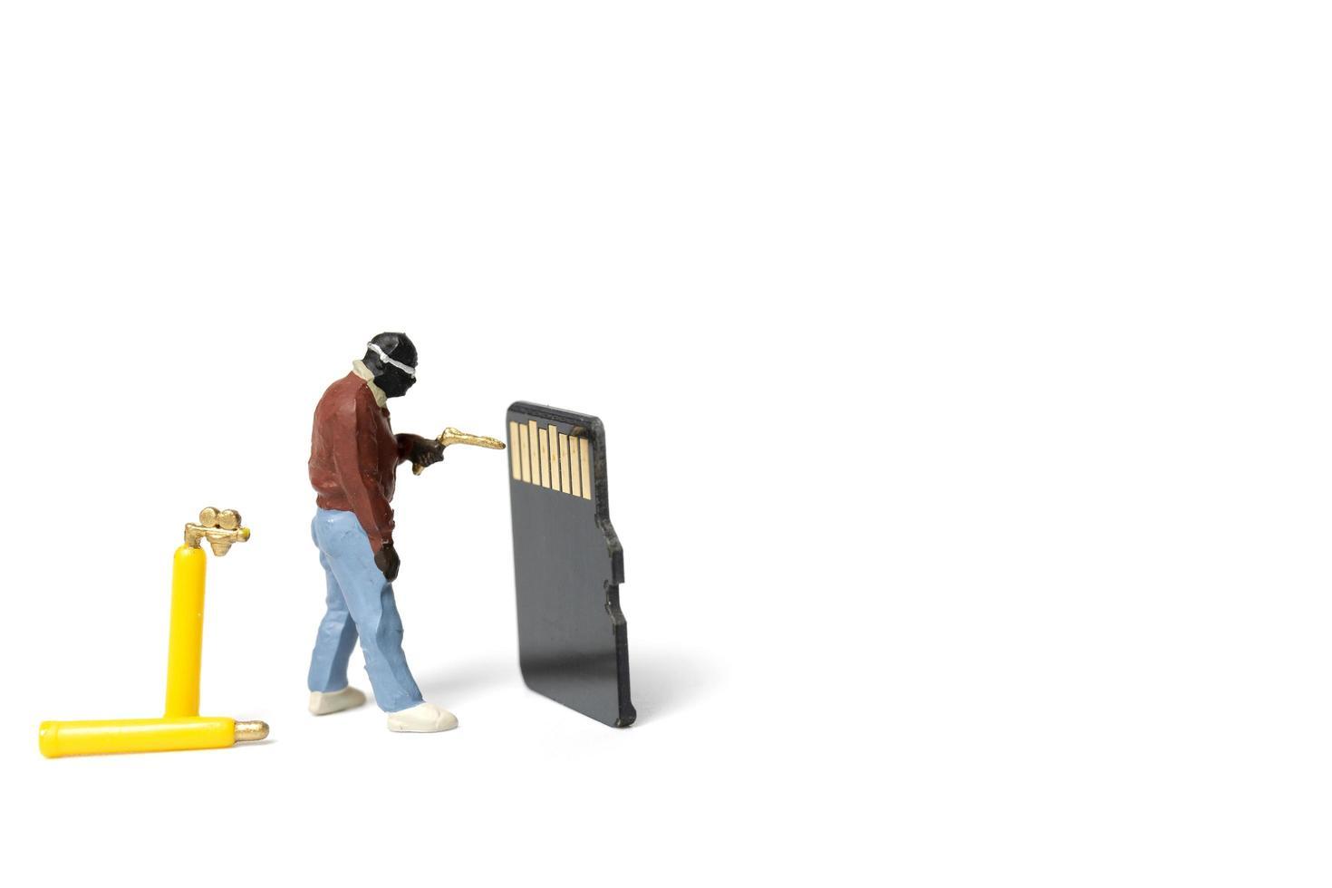 Miniaturtechniker, der Stapel-SD-Karten auf einem weißen Hintergrund fixiert foto