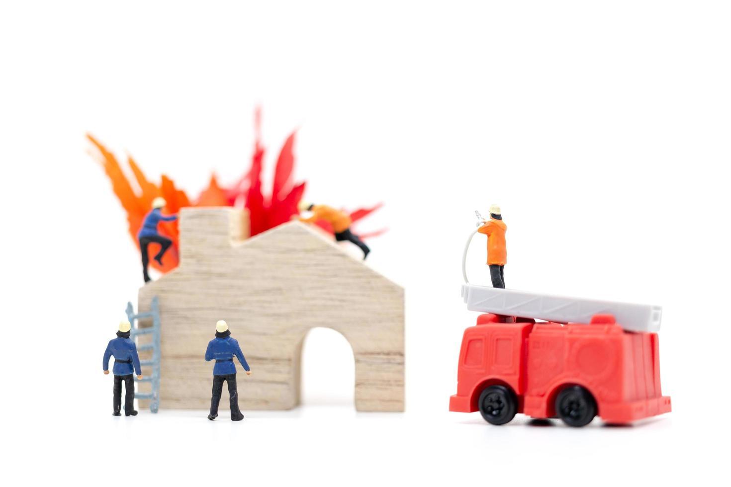 Miniatur-Feuerwehrleute, die sich um einen Brand in einem Holzhaus kümmern foto