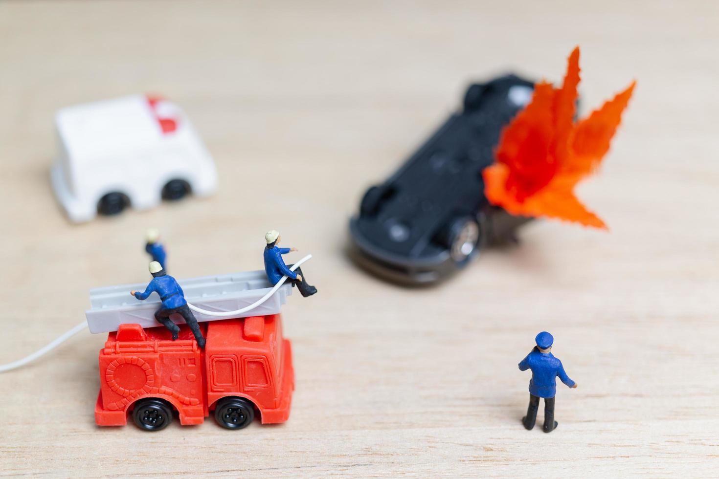 Miniatur Feuerwehrleute bei einem Autounfall, Autounfallkonzept foto