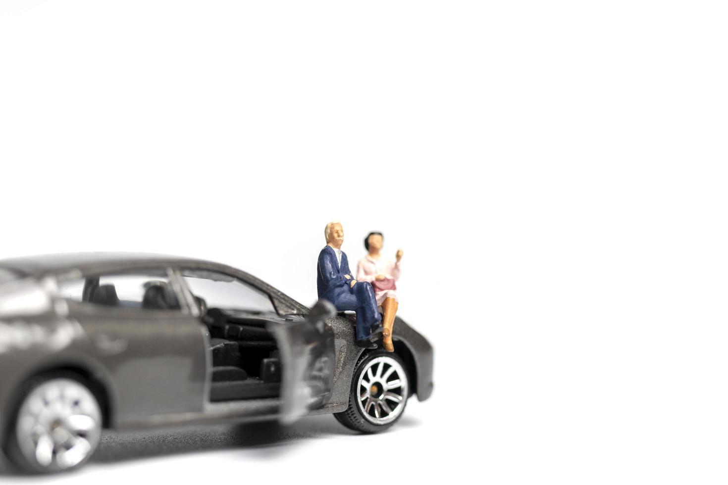 Miniaturmenschen, die auf einem Auto auf einem weißen Hintergrund sitzen foto