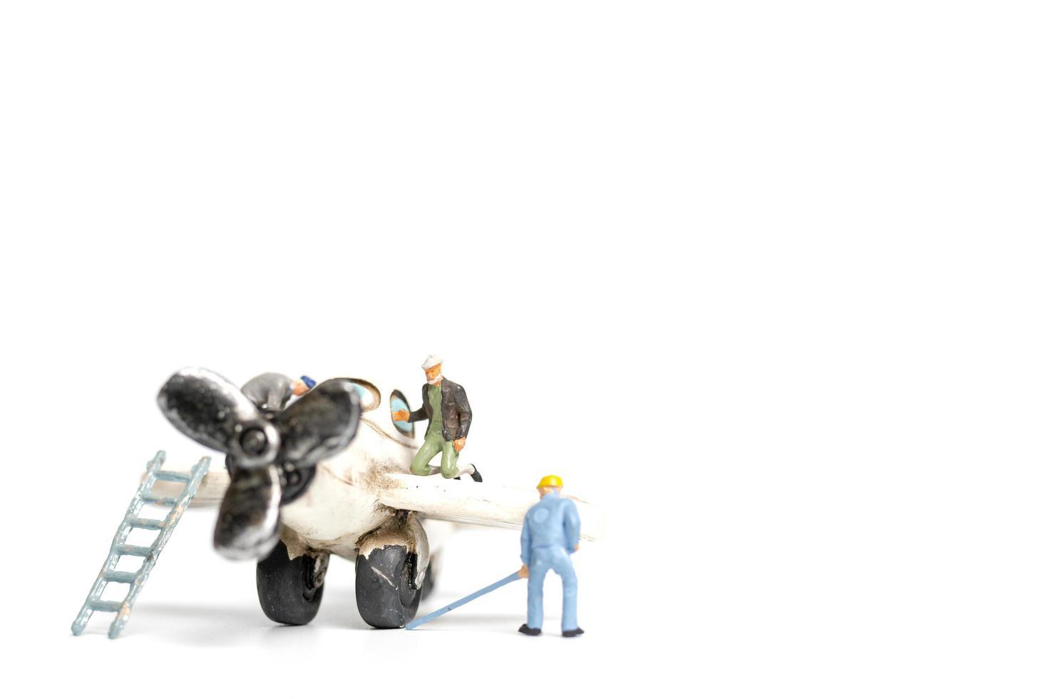 Miniaturarbeiter, die ein Spielzeugflugzeug auf einem weißen Hintergrund reparieren foto