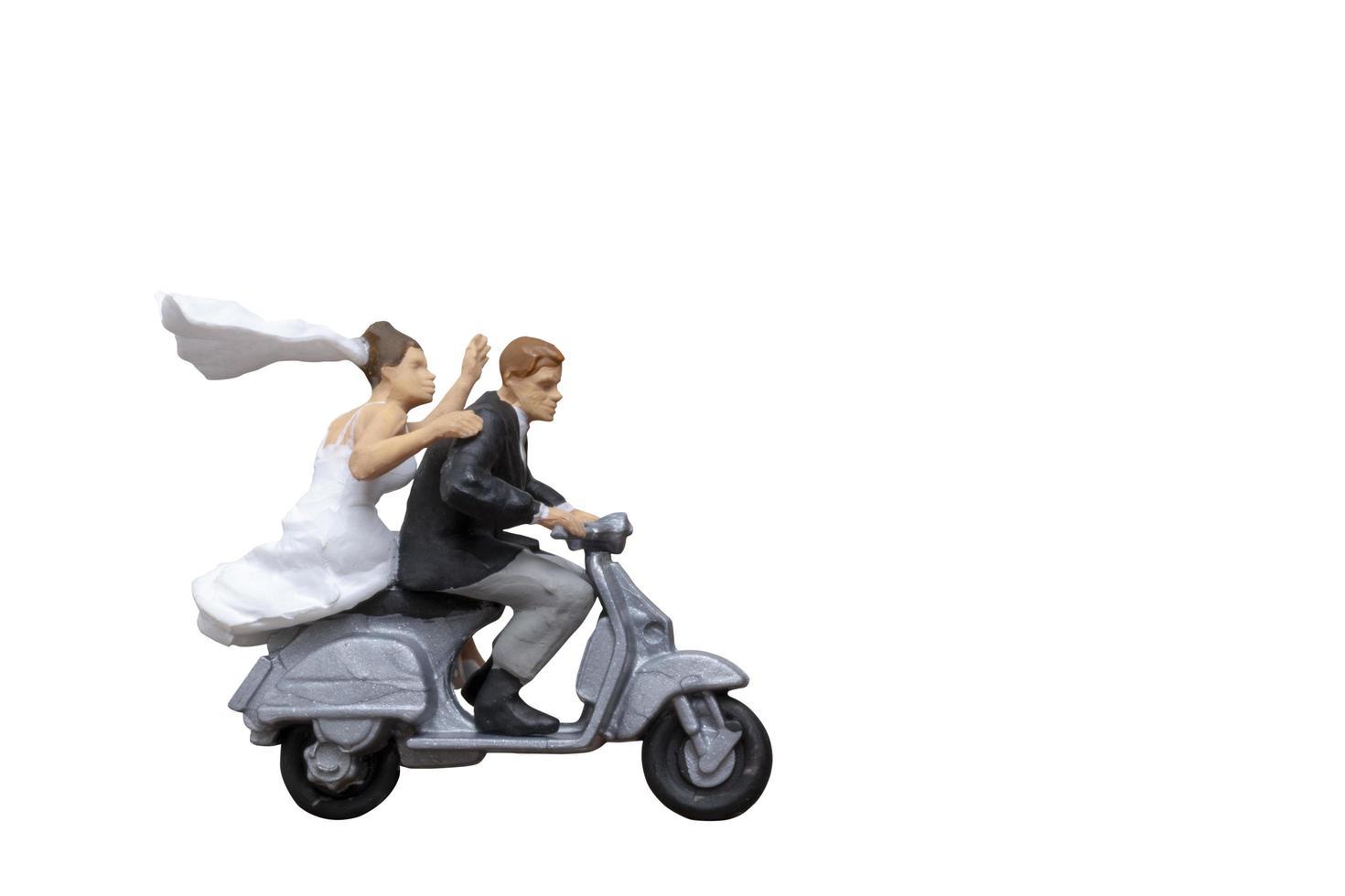 Miniaturpaar, das ein Motorrad auf lokalisiertem weißem Hintergrund reitet foto