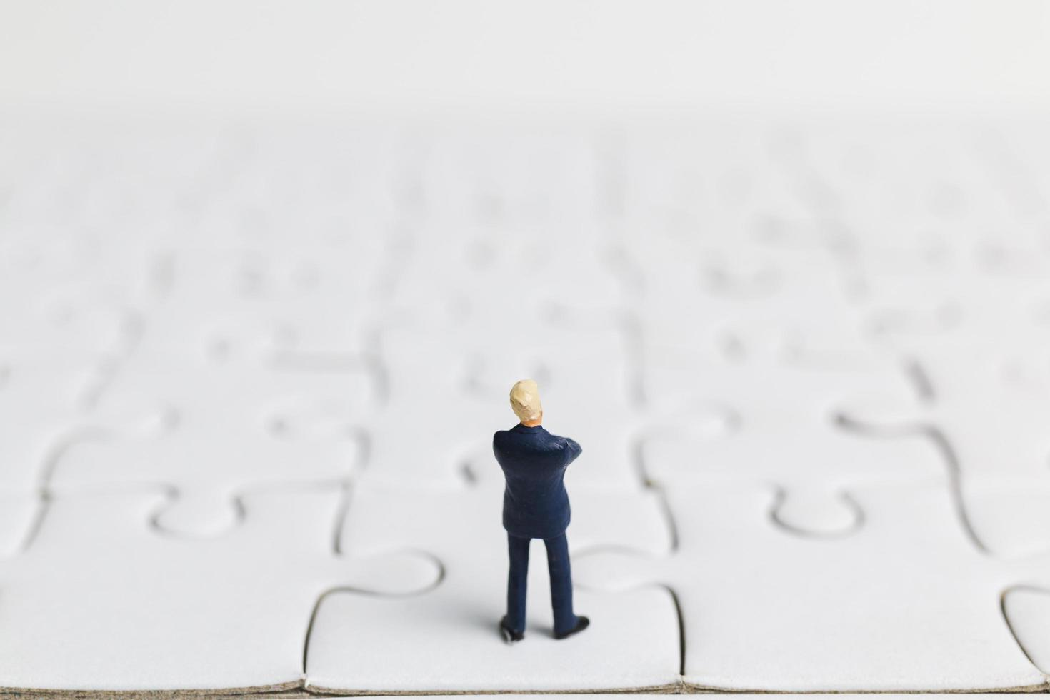 Miniaturgeschäftsmann, der auf einem weißen Puzzle, Geschäftskonzept steht foto
