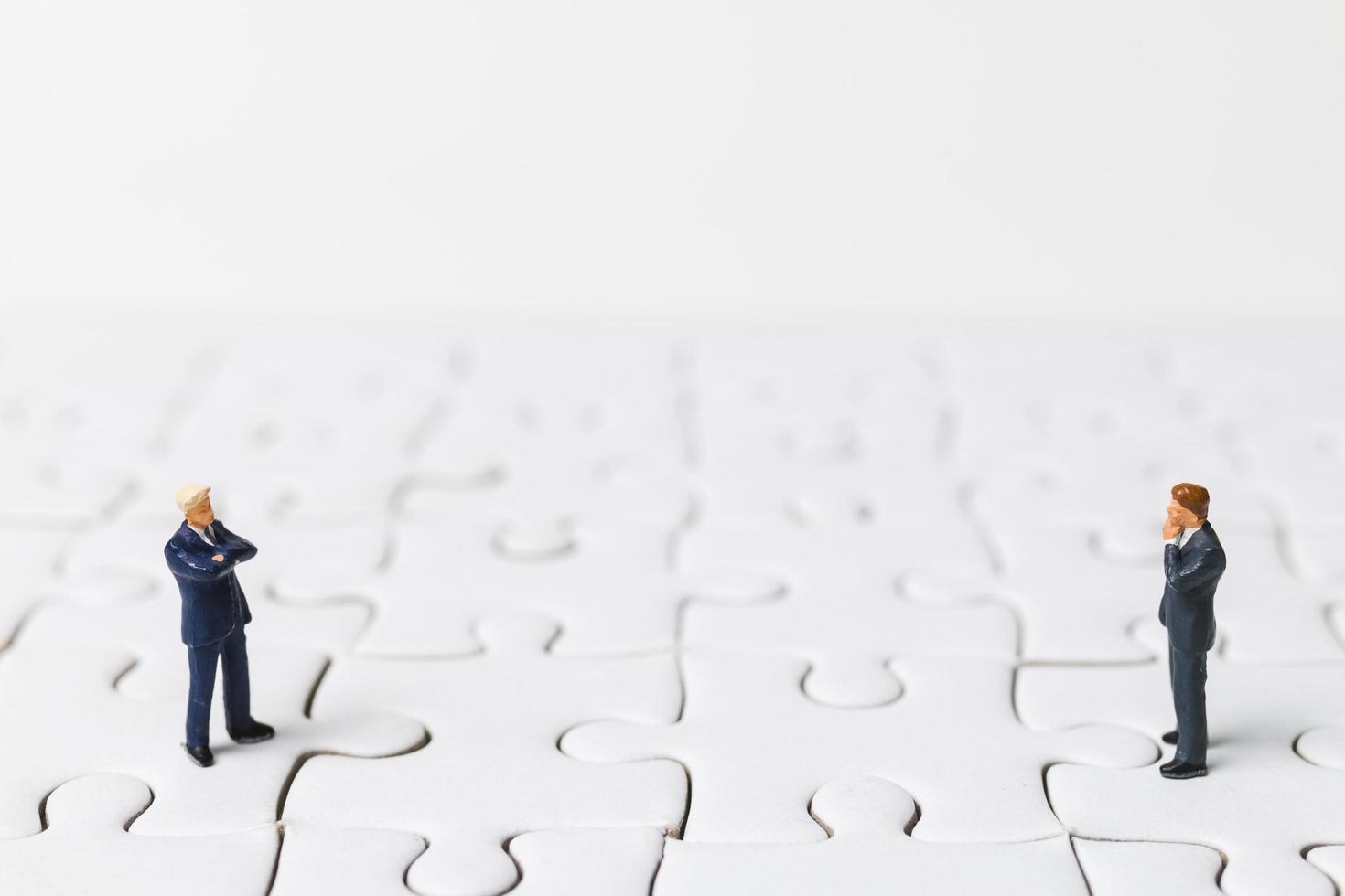 Miniaturgeschäftsleute, die auf einem weißen Puzzle stehen, Geschäftskonzept foto