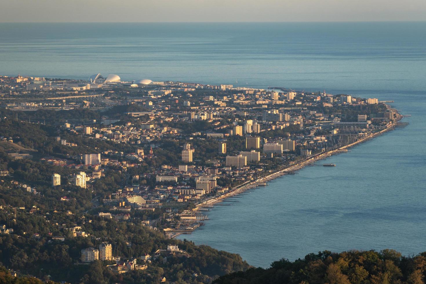 Luftaufnahme von Bergen und entfernter Stadt neben Gewässern in Sotschi, Russland foto