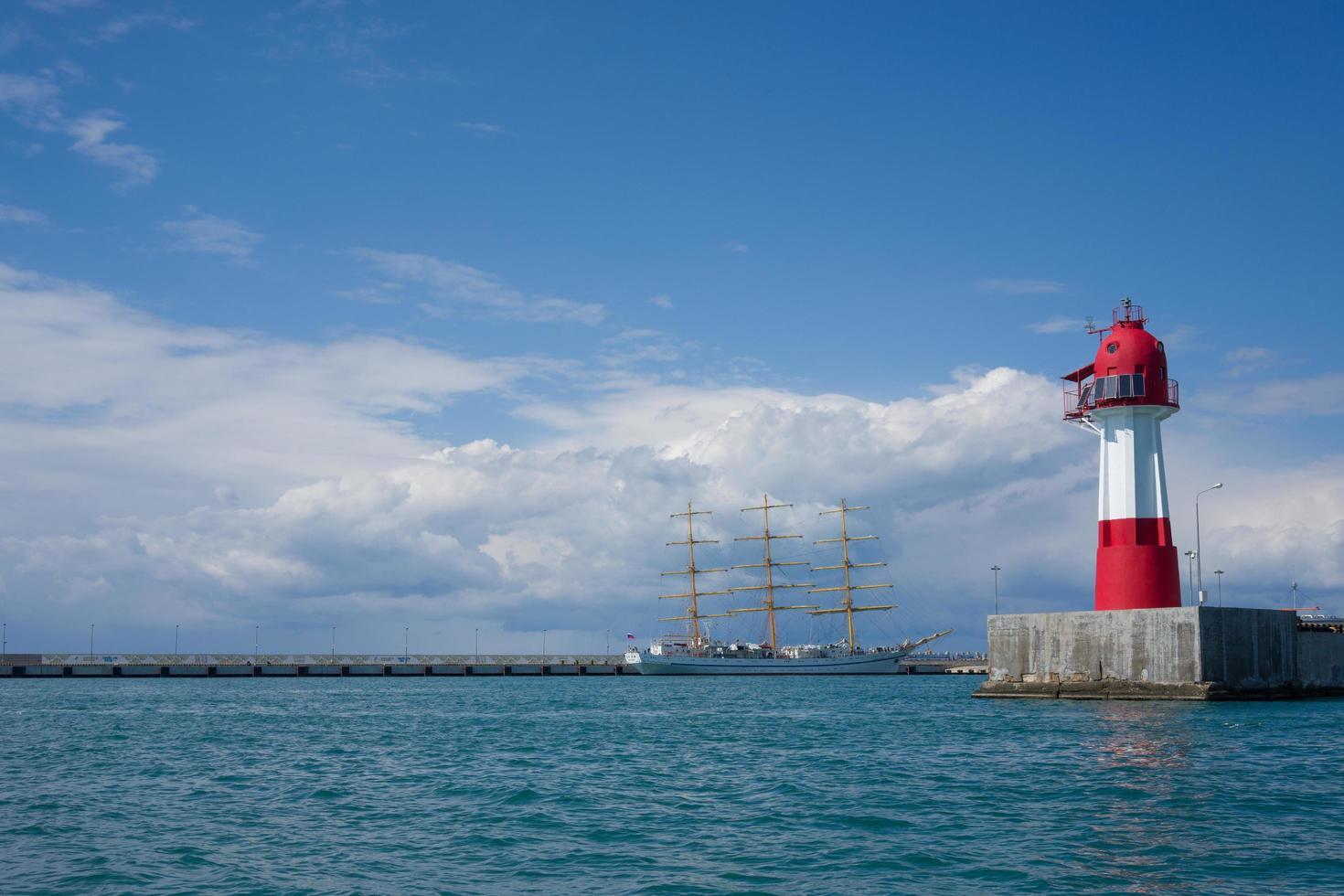 Seestück mit Vintage Segelboot und einem Leuchtturm mit einem wolkigen blauen Himmel in Sotschi, Russland foto