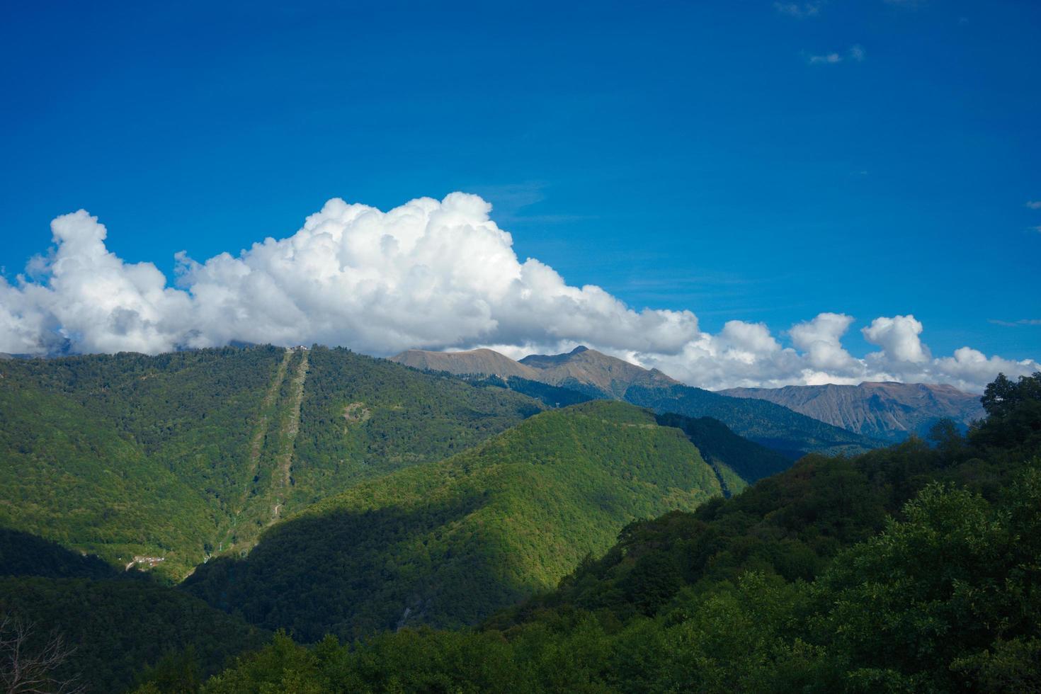 Berglandschaft mit grünem Wald und bewölktem blauem Himmel in Sotschi, Russland foto