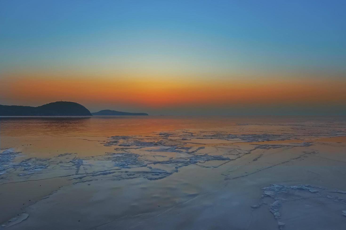Seelandschaft mit buntem orangefarbenem Sonnenuntergang und Bergen mit Eisschollen im Meer in Wladiwostok, Russland foto