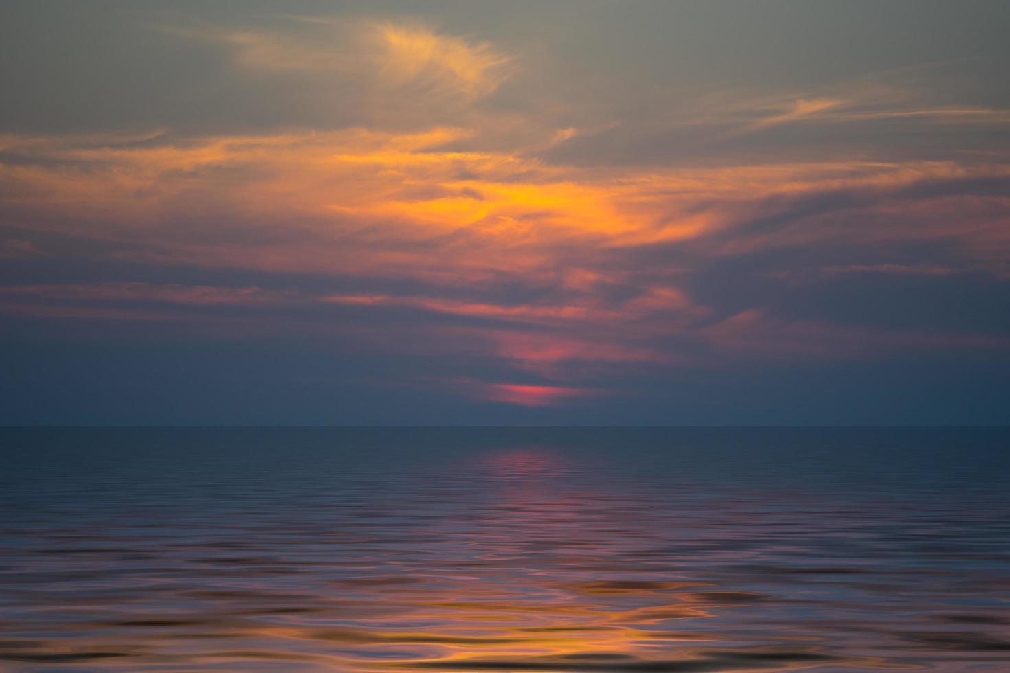 dunkelorange bewölkter Sonnenuntergang über einem Gewässer foto