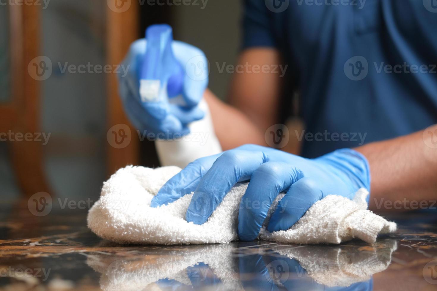 Geben Sie blaue Gummihandschuhe in die Hand, halten Sie die Sprühflasche und reinigen Sie einen Tisch foto