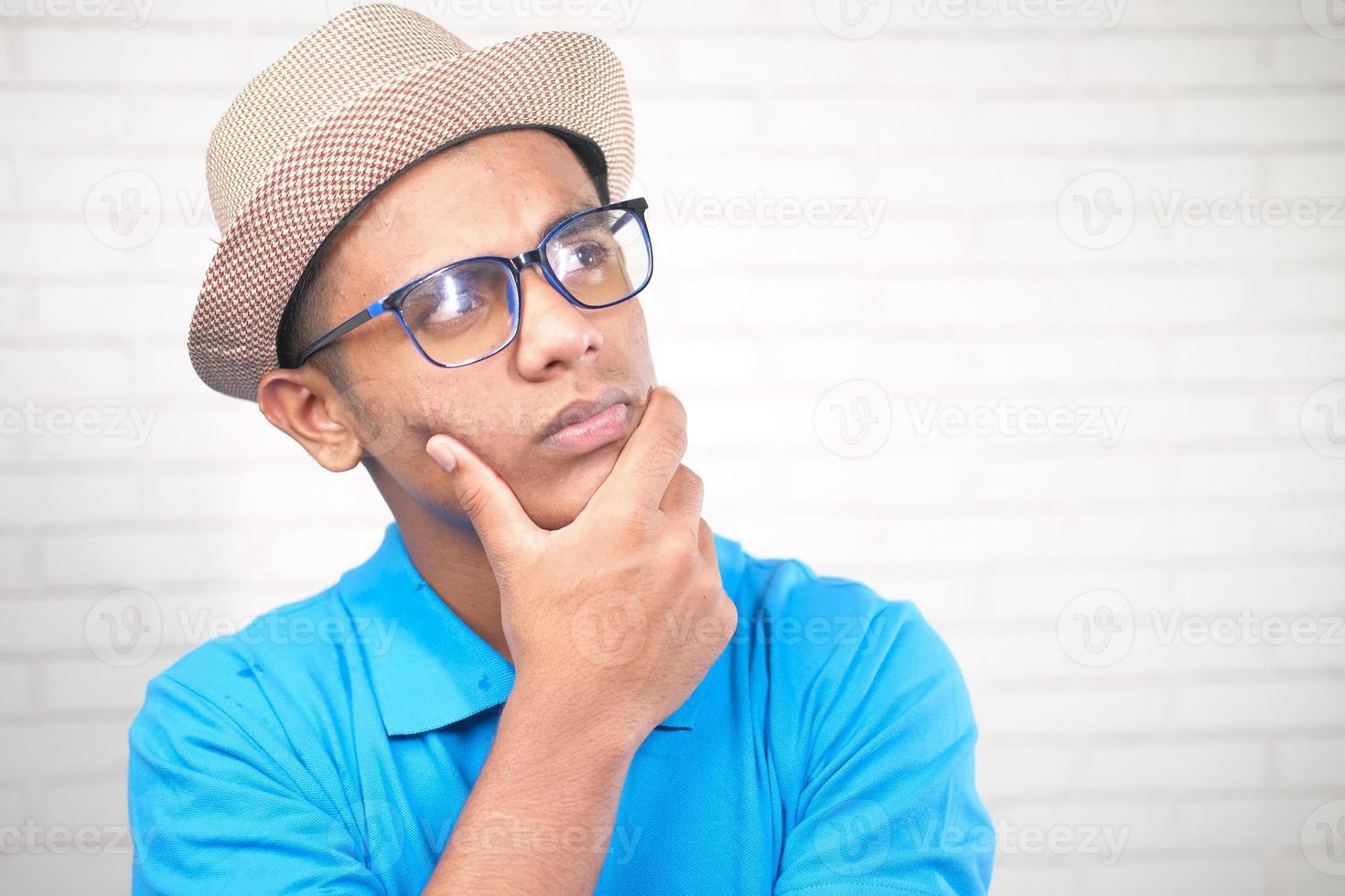 nachdenklicher Mann mit Hut und Brille, der wegschaut foto
