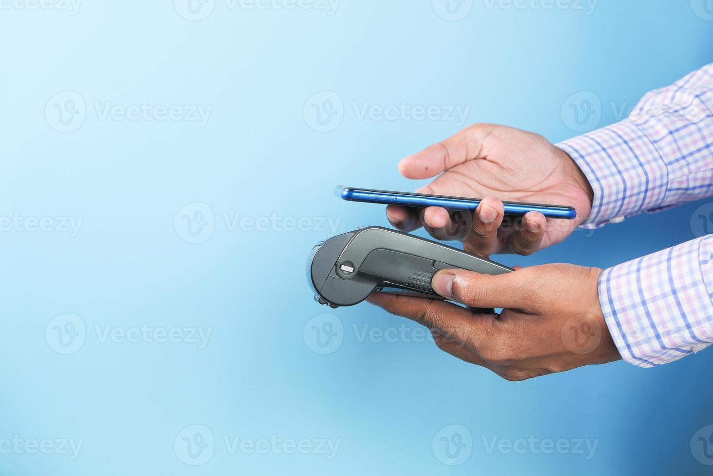 Mann, der Telefon benutzt, um auf blauem Hintergrund zu bezahlen foto