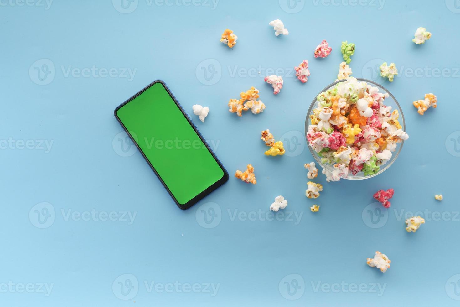 Draufsicht von Smartphone und Popcorn auf blauem Hintergrund foto