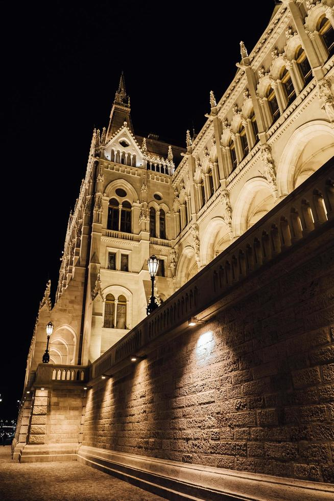 das ungarische parlament in budapest an der donau im nachtlicht der straßenlaternen foto