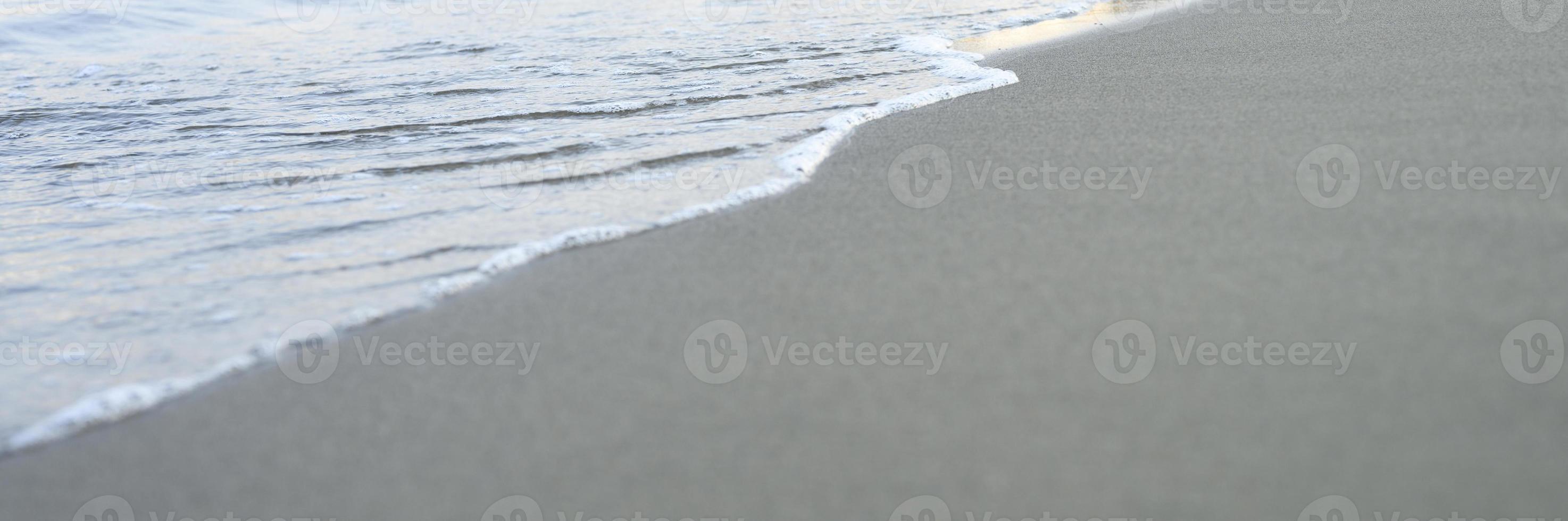 verschwommene Welle des Meeres am abendlichen Sandstrand foto
