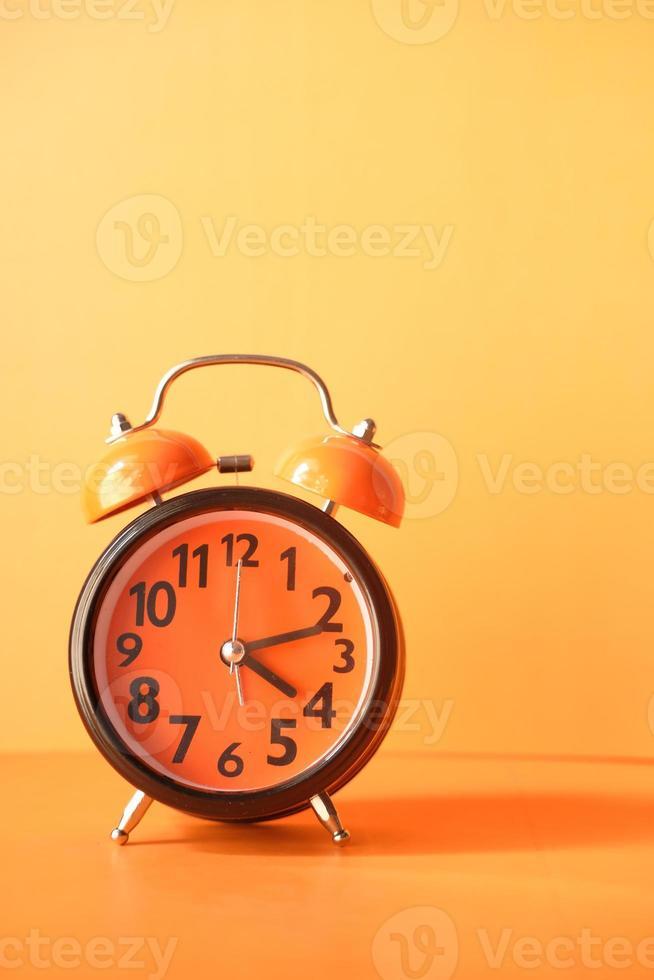 alter Wecker auf orangefarbenem Hintergrund foto