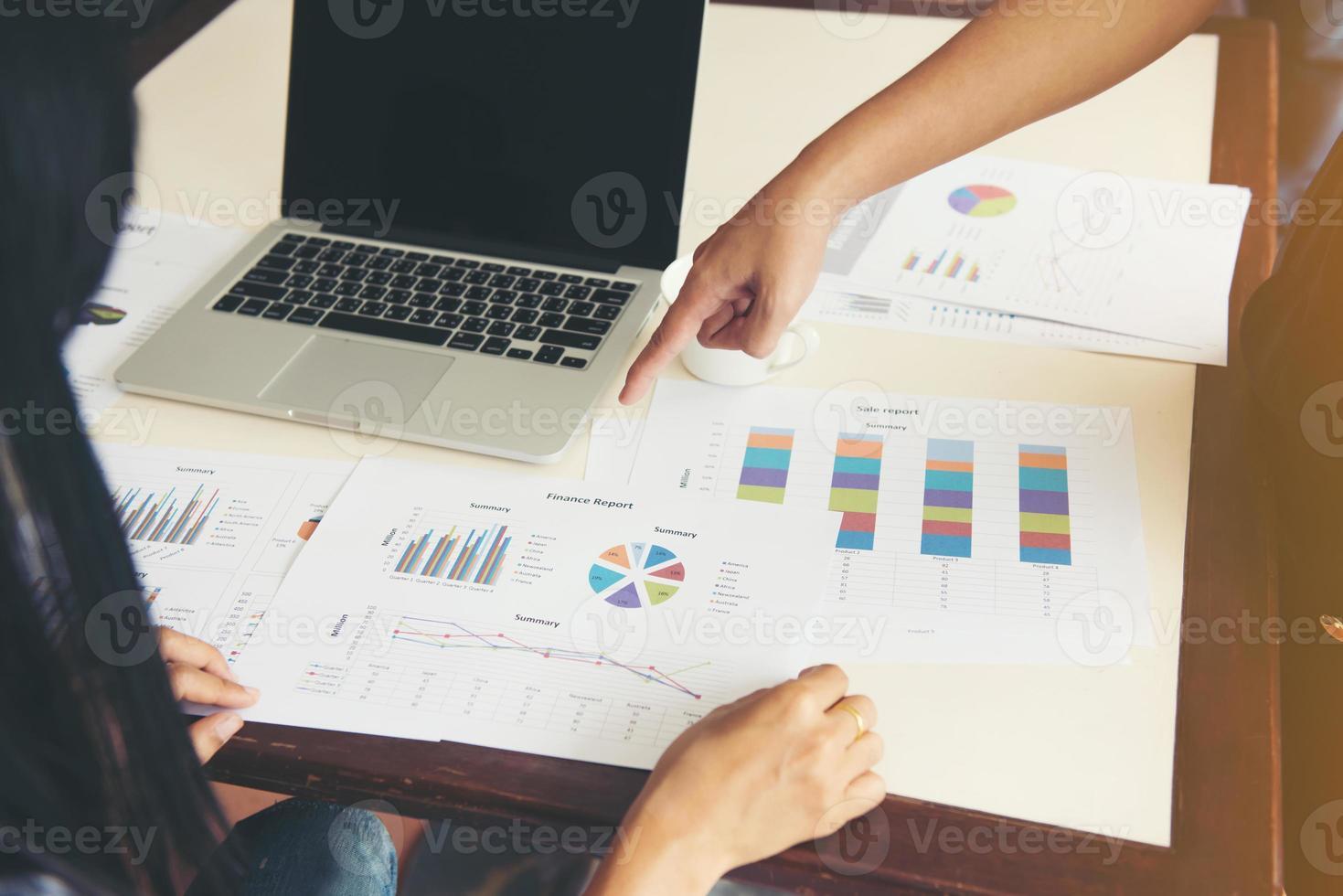Hand zeigt auf ein Diagramm während eines Geschäftstreffens foto