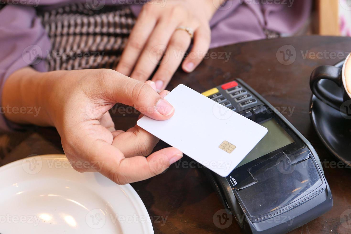 Person, die Kreditkarte in einem Café verwendet foto