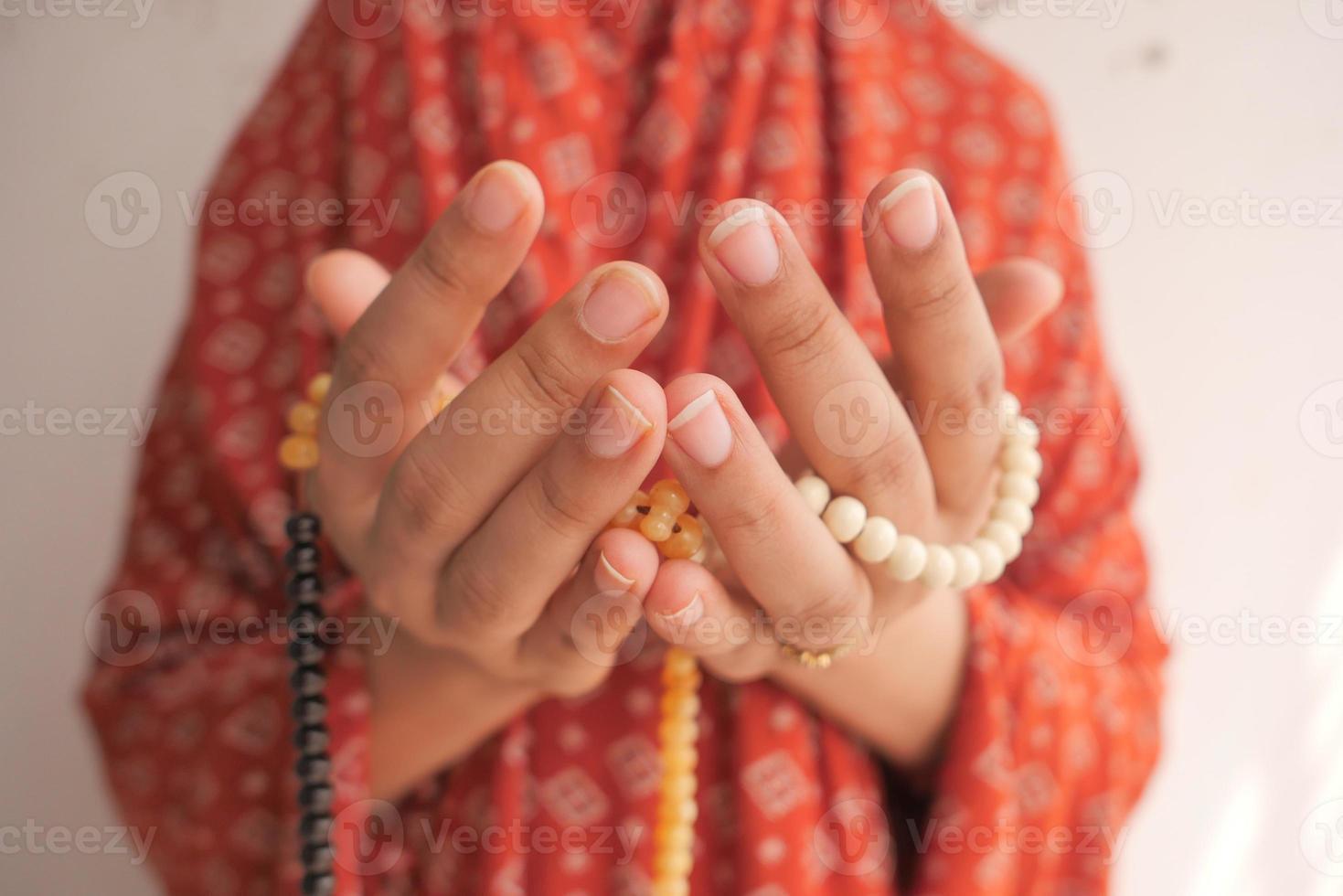 Nahaufnahme der Hände, die mit Perlen beten foto