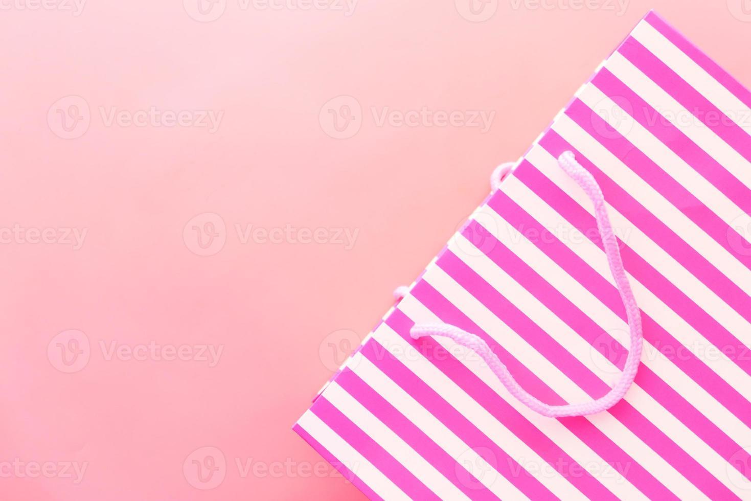 rosa gestreifte Geschenktüte auf rosa Hintergrund foto