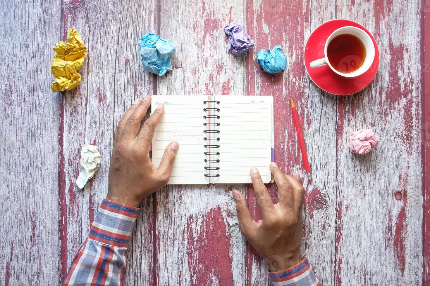 zerknitterte Papierkugeln und Notizblock auf Holztisch foto