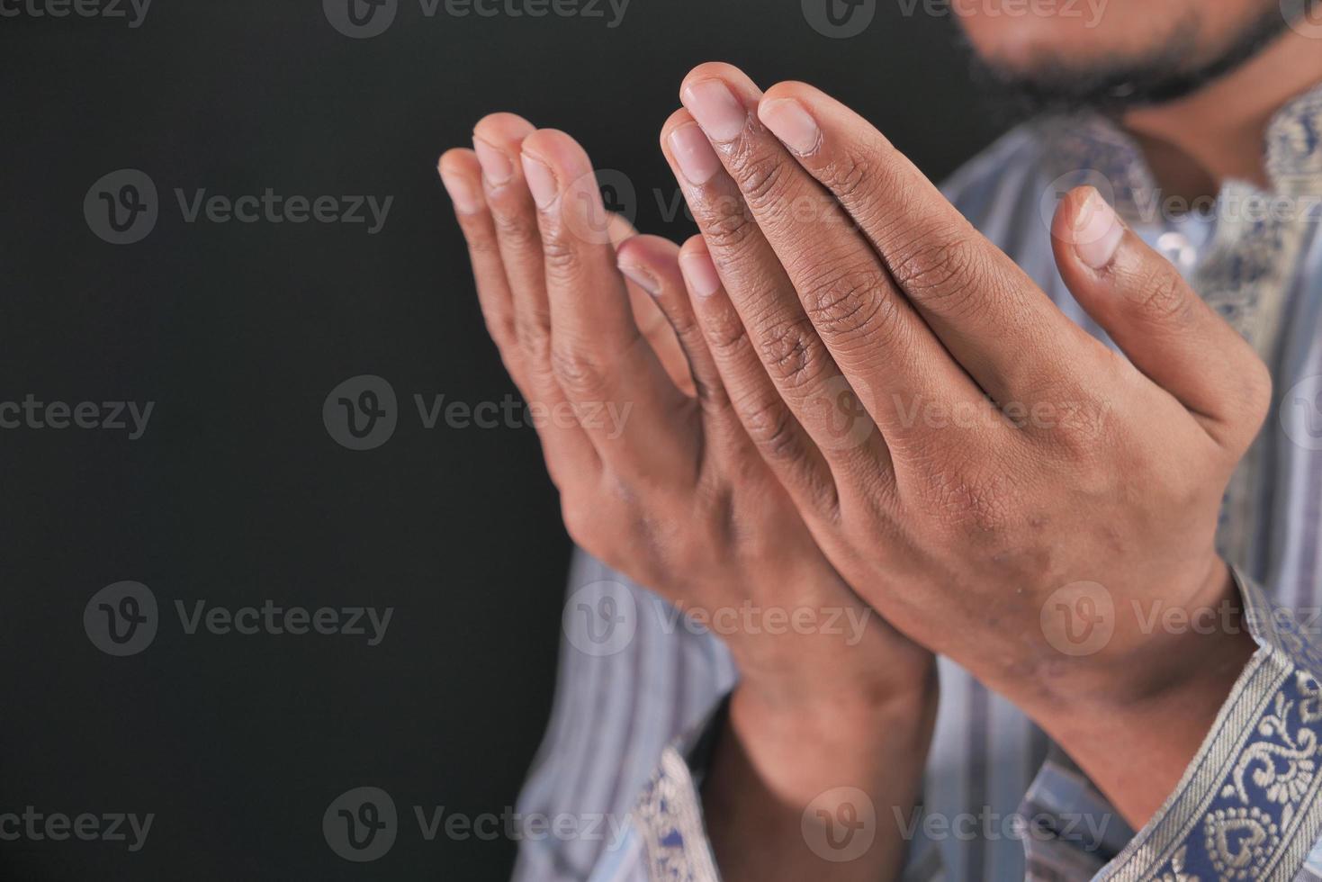 Männerhände, die auf schwarzem Hintergrund beten foto