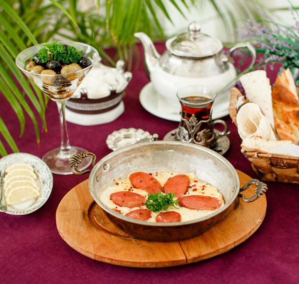 türkische Wurst mit Eiern in Stahlpfanne, Teekanne, Oliven und Brot foto