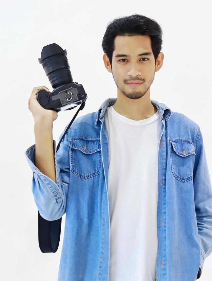 schöner junger Fotograf, der mit einer Kamera auf einem weißen Hintergrund steht foto