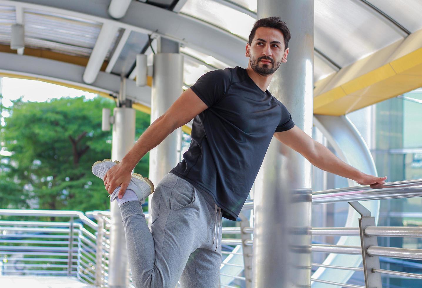 Der hübsche junge Mann trägt Sportbekleidung und trainiert im Freien foto