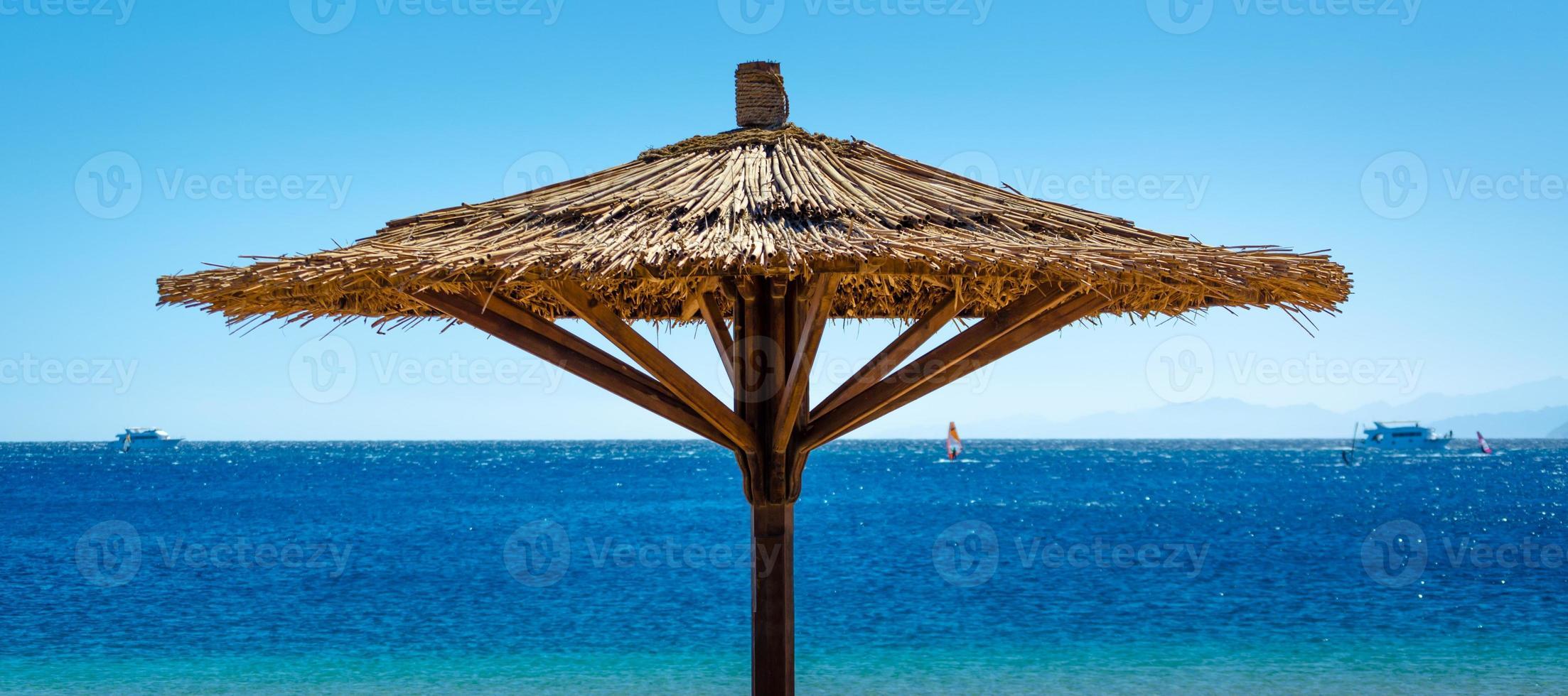 Schilf-Sonnenschirm gegen das blaue Meer in Ägypten foto