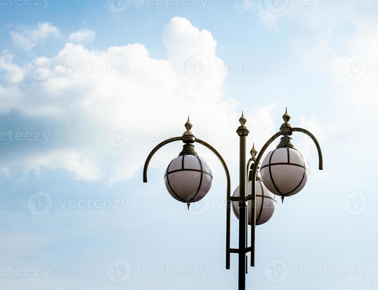 Straßenlaterne gegen einen blauen Himmel und weiße Wolken foto