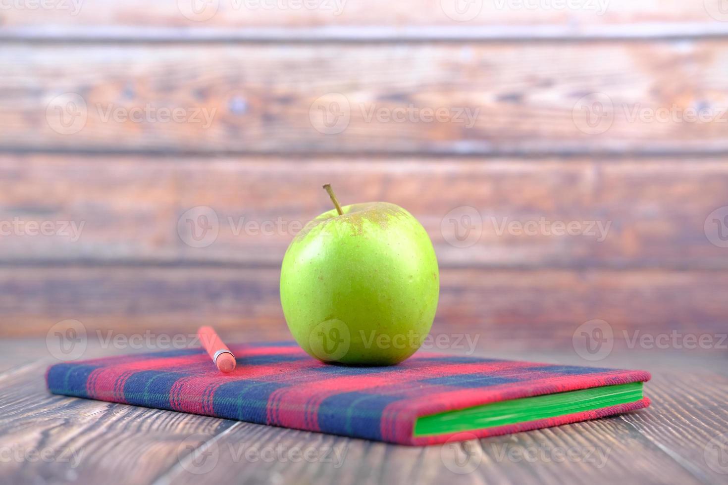 Apfel auf Notizblock auf Tisch foto