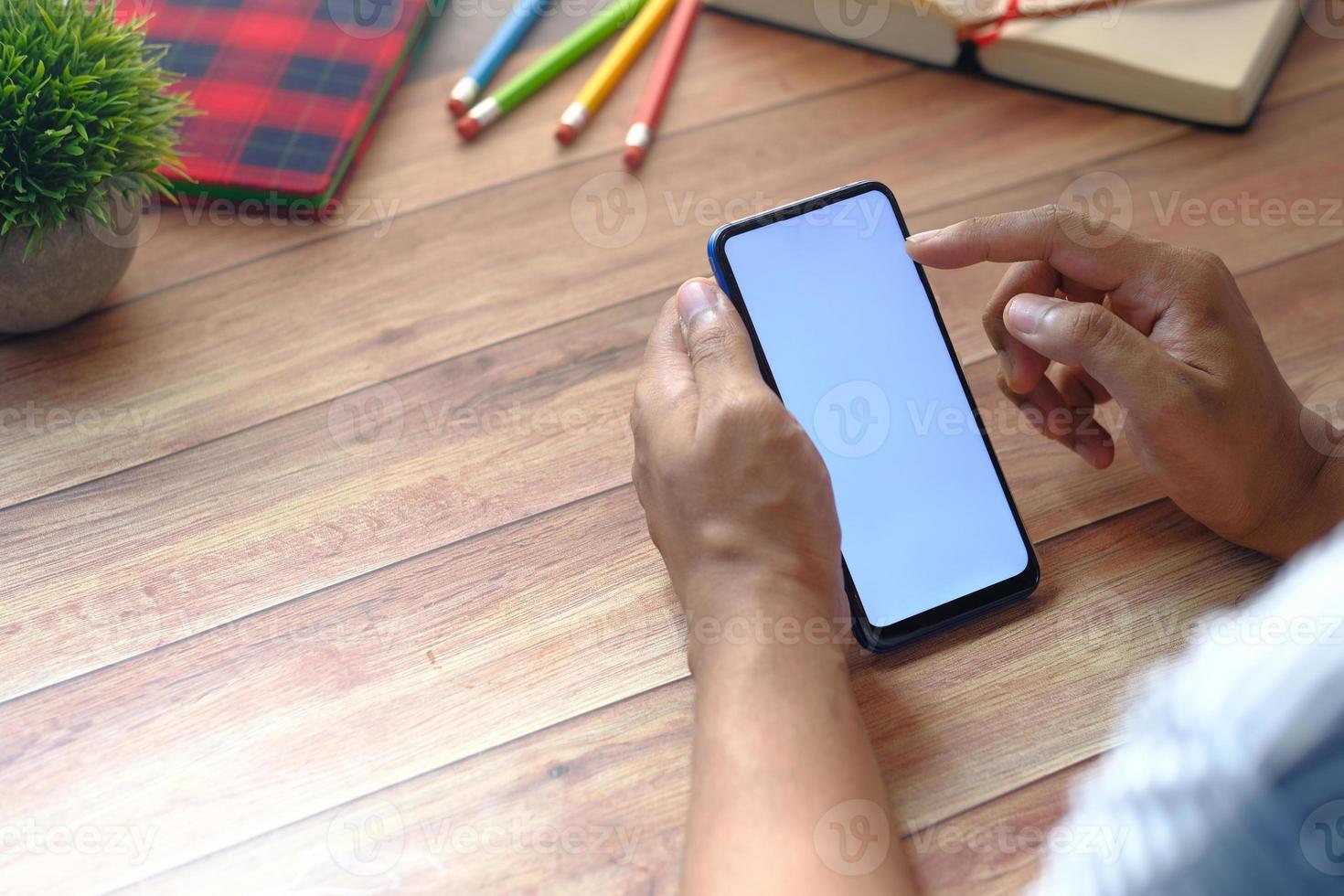 Rückansicht der Hand, die Smartphone auf hölzernem Hintergrund hält foto