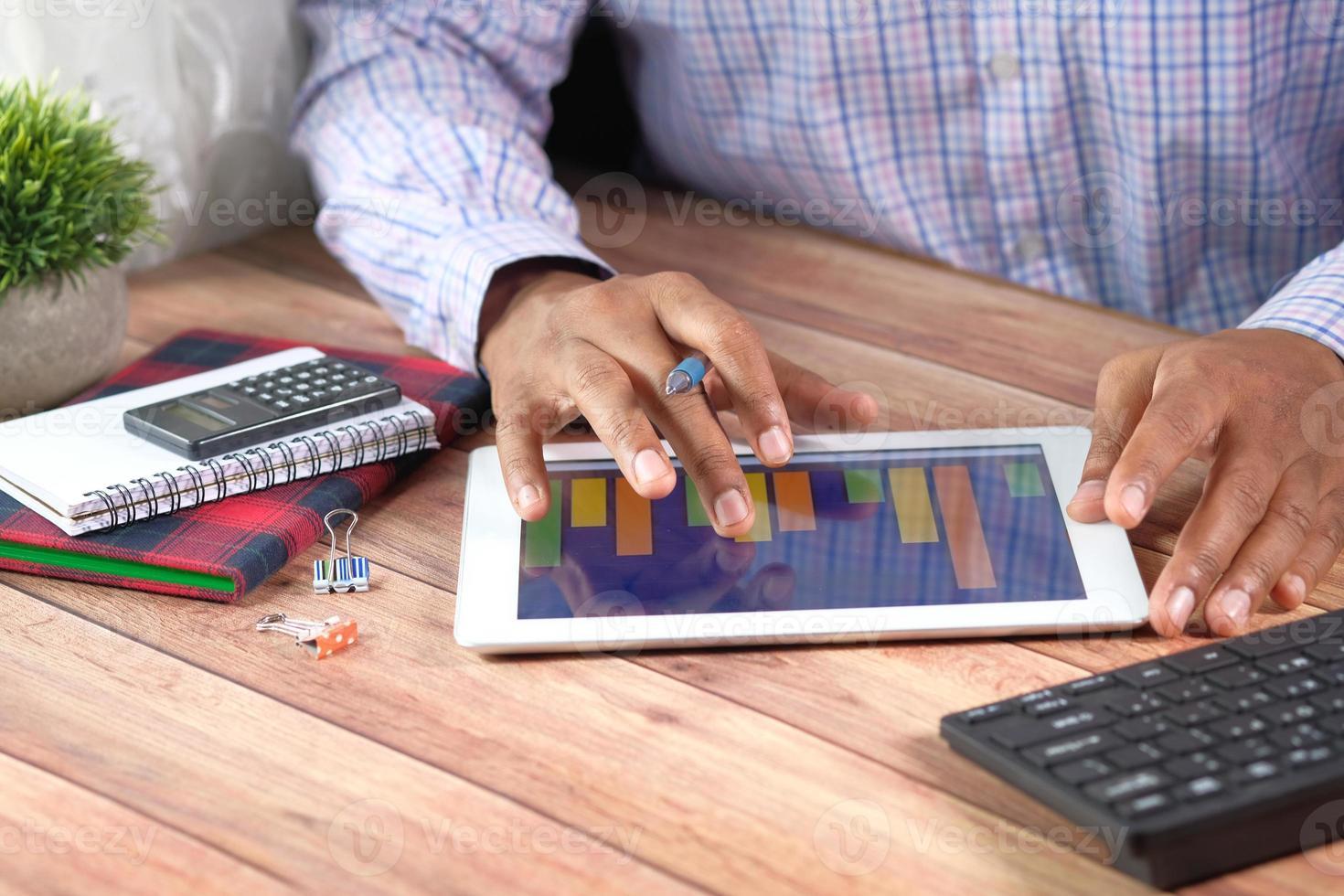 Geschäftsmann, der Diagramme auf digitalem Tablett am Schreibtisch analysiert foto