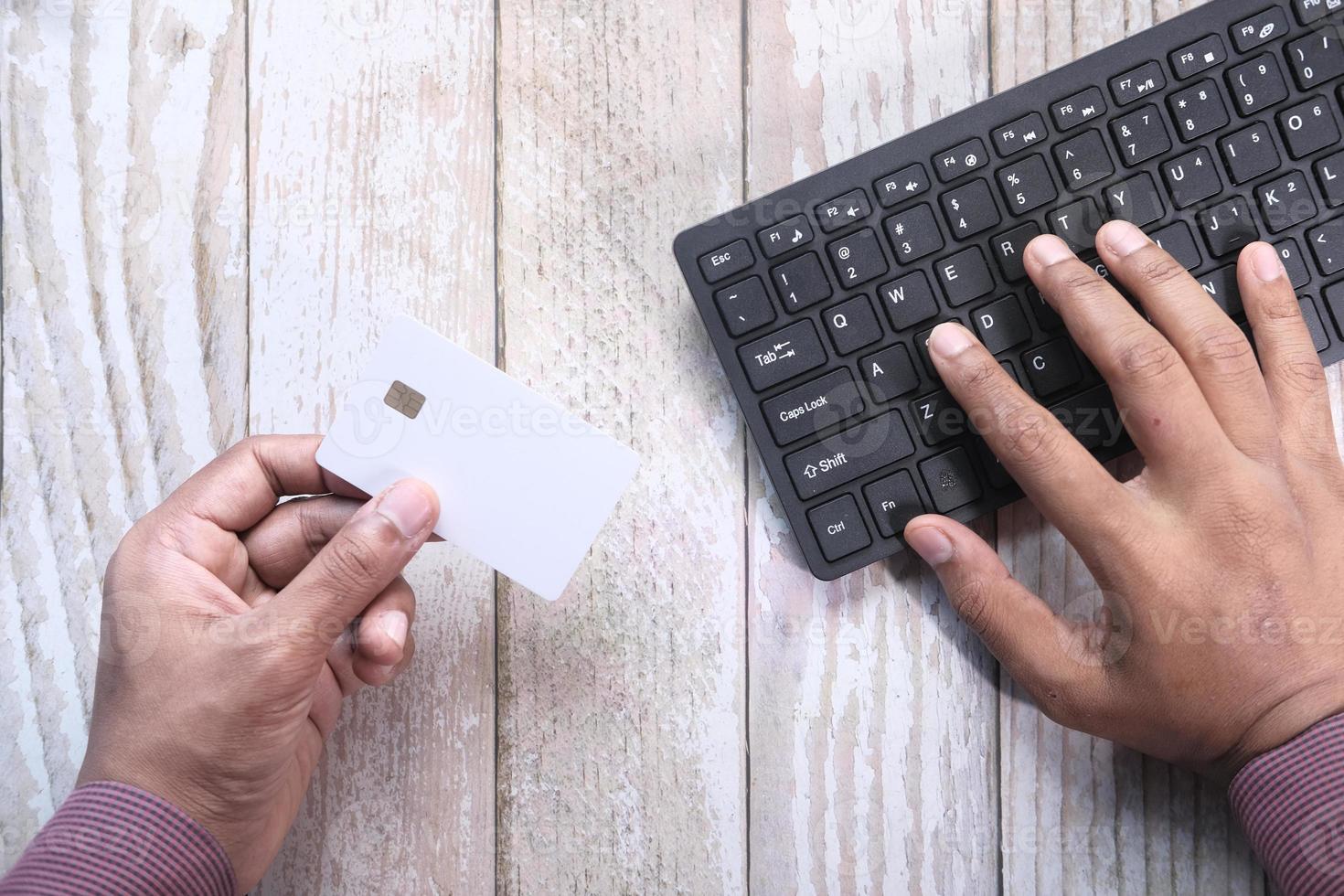 Mann mit Kreditkarte, um etwas online zu kaufen foto