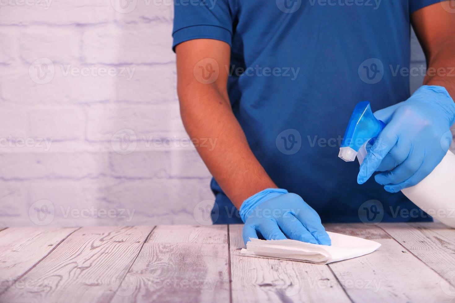 Person, die Desinfektionsspray verwendet, um die Tischoberfläche zu reinigen foto