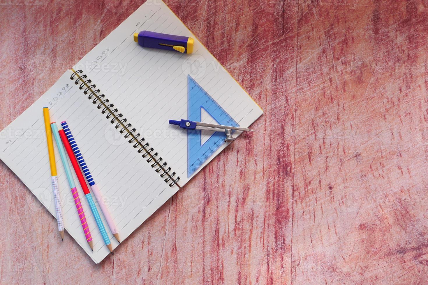 Draufsicht auf Schulmaterial auf Tisch mit Kopierraum foto