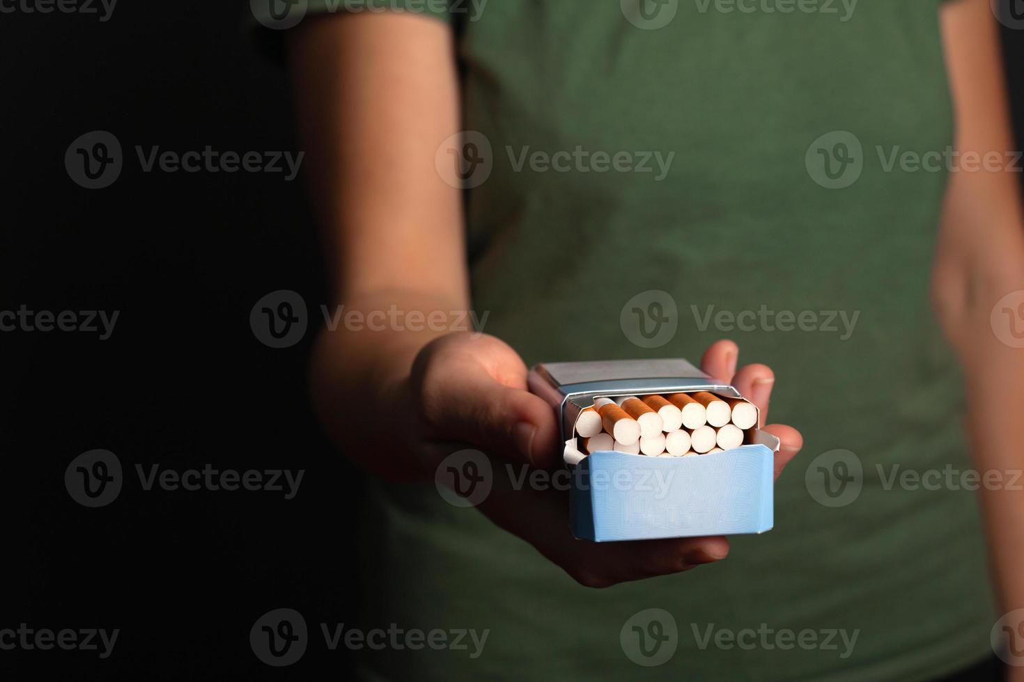 Hand eines Mädchens hält eine Packung Zigaretten schlägt vor, eine Wahl zu treffen foto