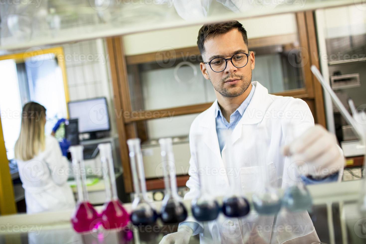 junger Forscher prüft Reagenzgläser foto