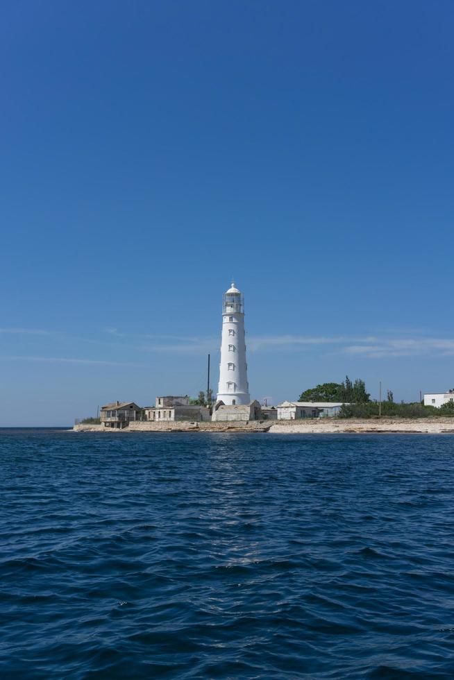 Seelandschaft eines weißen Leuchtturms am Kap Tarkhankut mit einem klaren blauen Himmel auf der Krim foto
